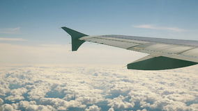 Airplane flying over the clouds. View from the window to the sky and aircraft wing. stock video footage