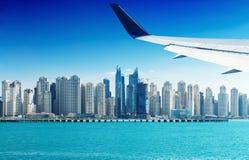 Airplane flying over Dubai skyscrapers, UAE Royalty Free Stock Photos