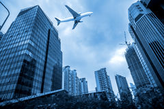 Airplane flying over high buildings Royalty Free Stock Images