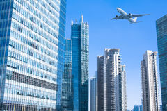 Airplane flying over high buildings Stock Photo