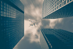 Airplane flying over high rise building Stock Photography