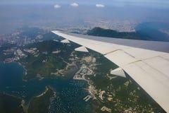 Airplane flying over hong kong Stock Photos