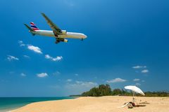 Airplane flying over the island beach Stock Photography