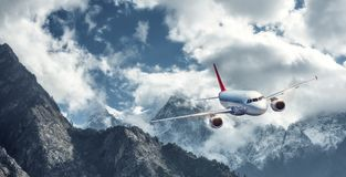 Airplane is flying over low clouds against mountains Royalty Free Stock Image