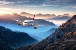 Airplane is flying over mountains in fog at colorful sunset. In summer. Landscape with passenger airplane, hills in low clouds, blue sky. White aircraft royalty free illustration