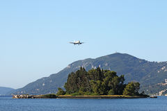 Airplane flying over Mouse island Corfu Royalty Free Stock Photo