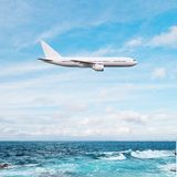 Airplane flying over ocean Stock Photo