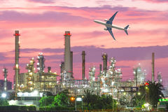 Airplane flying over oil refinery industry plant along twilight Stock Photography