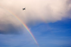 Airplane flying over rainbow Royalty Free Stock Image