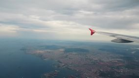 Airplane flying over the sea and the city, view from the window. Airplane flying over the sea and the city in the cloudy sky, view from the window stock video footage
