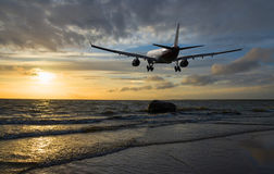 Airplane flying over the sea Stock Photography