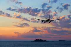 Airplane flying over the sea at sunset Royalty Free Stock Image