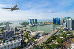 Airplane flying over Singapore city in morning time. Royalty Free Stock Images