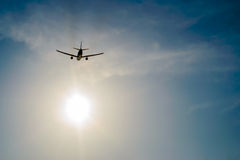 Airplane flying over the sky and sun rays background Stock Photography