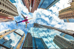 Airplane flying over skyscrapers royalty free stock photos