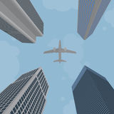 Airplane flying over skyscrapers Stock Photos