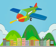 Airplane flying over a town Royalty Free Stock Images