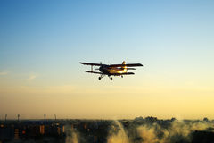 Airplane flying over town silhouette. Silhouette of red vintage airplane flying over town spraying insects stock photo