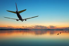 Airplane flying over tropical sea at beautiful sunset or sunrise Stock Image