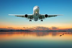 Airplane flying over tropical sea at beautiful sunset or sunrise Stock Photos
