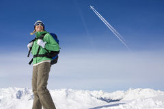 Airplane flying over woman backpacking on snowy mountain royalty free stock photography