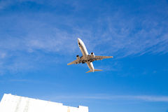 Airplane Flying Overhead with Blue Sky Royalty Free Stock Photo