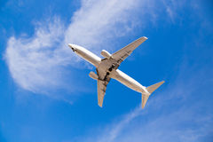 Airplane Flying Overhead with Blue Sky Royalty Free Stock Photography