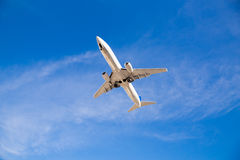 Airplane Flying Overhead with Blue Sky Stock Photography