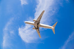 Airplane Flying Overhead with Blue Sky Royalty Free Stock Image