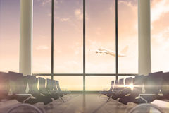 Airplane flying past departures lounge window Royalty Free Stock Photos