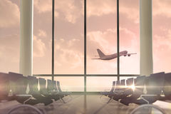 Airplane flying past departures lounge window Stock Image