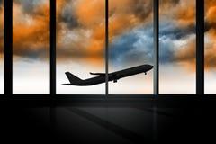 Airplane flying past window in orange sky Stock Photos