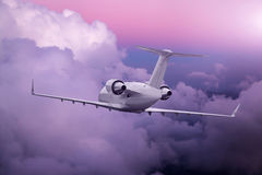 Airplane flying at purple sunset over mountains and sea Royalty Free Stock Photography