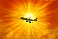 Airplane Flying Sky. An airplane flying through a orange sky with the sun and clouds in the background Royalty Free Stock Images