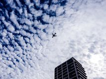 Airplane flying in the sky above the skyscraper. Tel-Aviv, Israel royalty free stock images