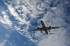 Airplane flying in sky with  clouds Royalty Free Stock Photography