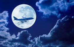 Airplane Flying Sky Moon. Air travel on an airplane flying through a night sky with moon and clouds in the background stock photos
