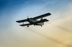 Airplane flying in the sky spraying mosquitoes.  Royalty Free Stock Image