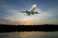 Airplane flying in the sky tropical sea at sunset time. Royalty Free Stock Image