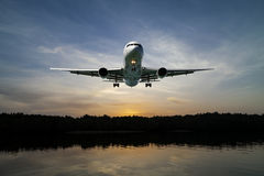 Airplane flying in the sky tropical sea at sunset time. Stock Photos