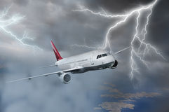 Airplane flying in storm. Passenger airplane flying above sea on stormy sky with dark clouds and lightnings Stock Image
