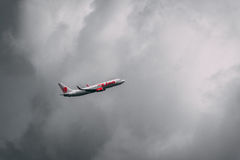 Airplane flying into the storm. Bangkok, Thailand - April 1, 2017: HS-LUO Boeing 737-800 of Thai Lion Airline depart from Don Muang Airport, Bangkok, Thailand royalty free stock photography