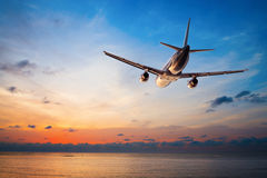 Airplane flying at sunset. Airplane flying above tropical sea at sunset Royalty Free Stock Photography