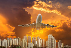 Airplane flying take off from runway on sunset over modern skyscrapers Royalty Free Stock Image