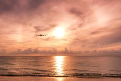 Airplane flying to arc sunlight on the sea at evening. Airplane flying to arc sunlight on the sea at sunset Stock Photo