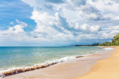 Airplane flying to exotic tropical beach Royalty Free Stock Photos