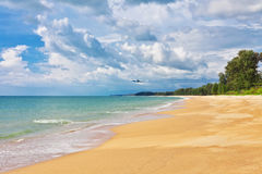 Airplane flying to exotic tropical beach Stock Photos