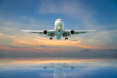 Airplane flying tropical sea at sunset time. Stock Photo