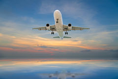 Airplane flying tropical sea at sunset time. Royalty Free Stock Images