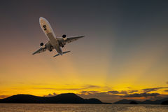Airplane flying tropical sea at sunset time. Royalty Free Stock Photo